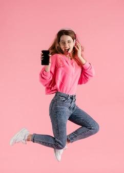 Portret szczęśliwa kobieta skacze i słucha muzyki