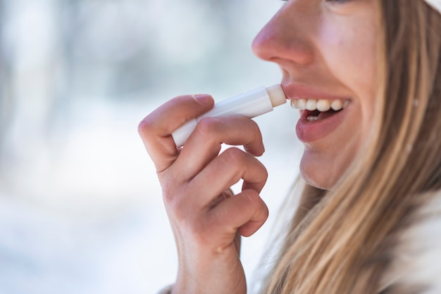 Portret szczęśliwa kobieta stosuje warga balsam w zimie z śnieżną górą
