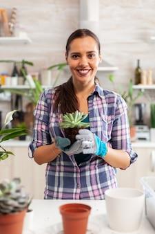 Portret szczęśliwa kobieta trzyma sukulenta, siedząc na stole w kuchni. kobieta przesadza kwiaty w ceramicznej doniczce za pomocą łopaty, rękawiczek, żyznej gleby i kwiatów do dekoracji domu.