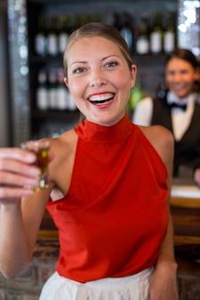 Portret szczęśliwa kobieta trzyma tequila strzelał przed baru kontuarem