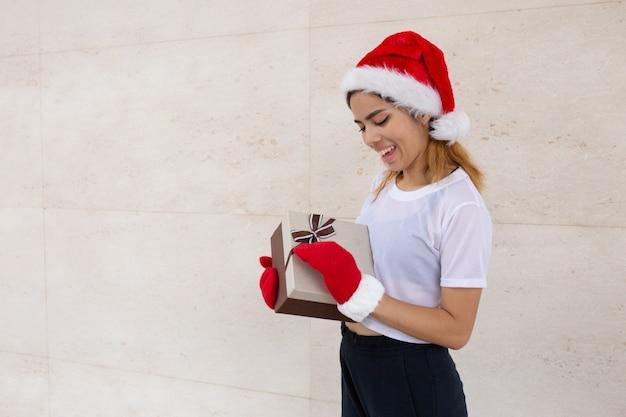 Portret szczęśliwa kobieta trzyma teraźniejszość w santa kapeluszu i mitynkach