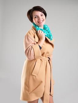 Portret szczęśliwa kobieta w beżowym jesiennym płaszczu z zielonym szalikiem na szarym tle