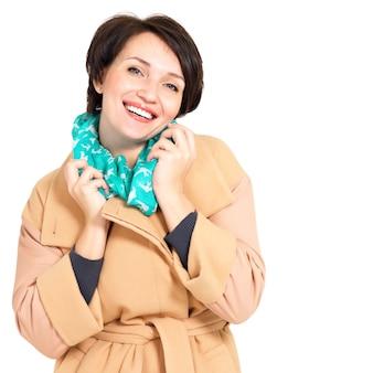 Portret szczęśliwa kobieta w jesienny płaszcz z zielonym szalikiem stojącym na białym tle