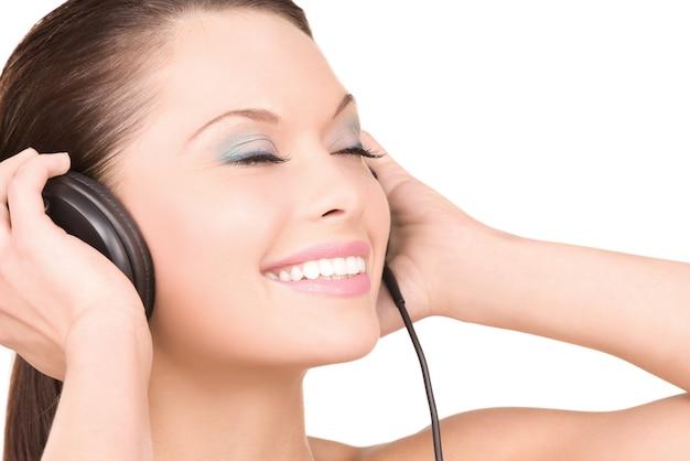 Portret szczęśliwa kobieta w słuchawkach na białej ścianie
