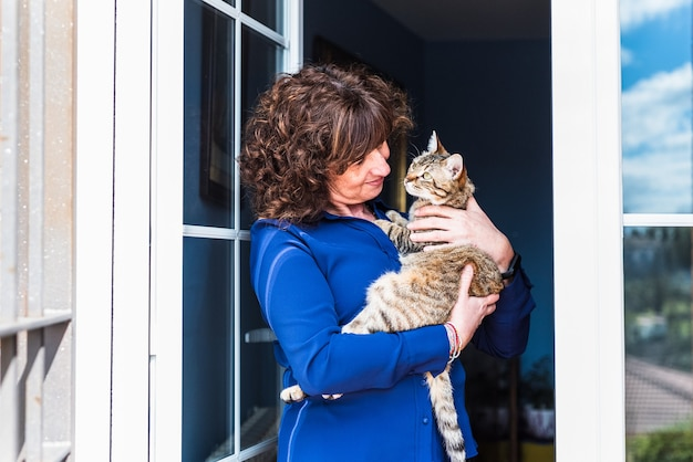 Portret szczęśliwa kobieta w średnim wieku trzyma jej kota