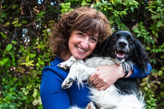 Portret szczęśliwa kobieta w średnim wieku z psem w ramionach