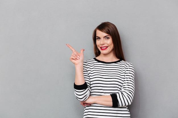 Portret szczęśliwa kobieta wskazuje palec daleko od