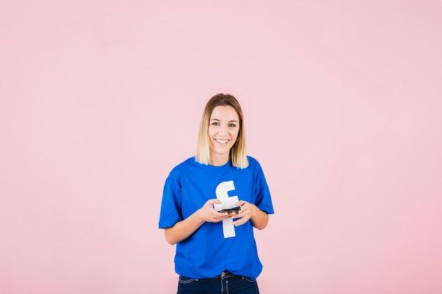 Portret szczęśliwa kobieta z facebook koszulką używać telefon komórkowego