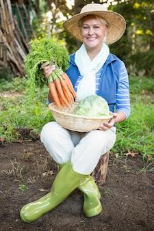 Portret szczęśliwa kobieta z marchewkami przy ogródem
