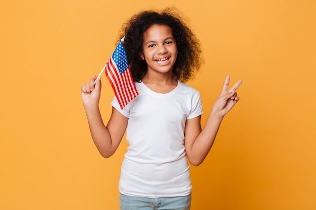 Portret szczęśliwa mała afrykańska dziewczyna trzyma flaga amerykańską