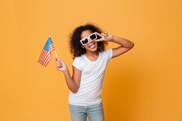 Portret szczęśliwa mała afrykańska dziewczyna w okularach przeciwsłonecznych z flaga amerykańską