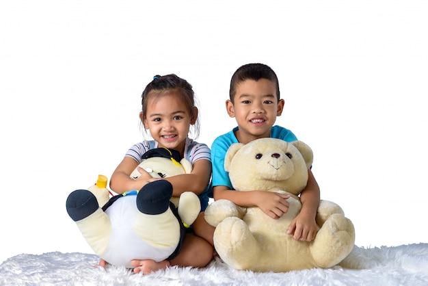 Portret szczęśliwa mała azjatykcia chłopiec i dziewczyna z dwa lalami odizolowywać na białym tle