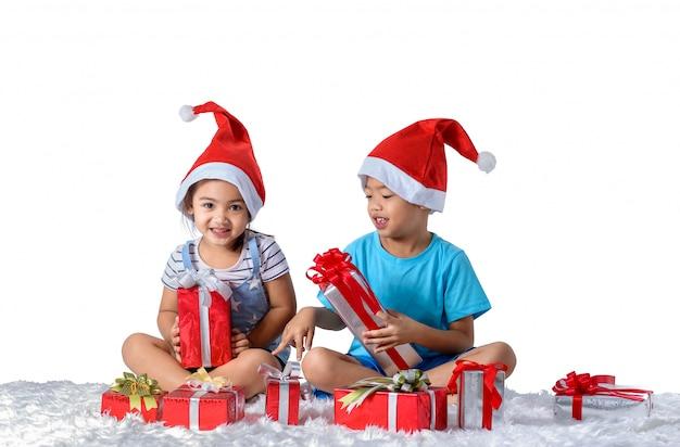 Portret szczęśliwa mała azjatykcia chłopiec i dziewczyna z wiele prezentów pudełkami odizolowywającymi na białym tle