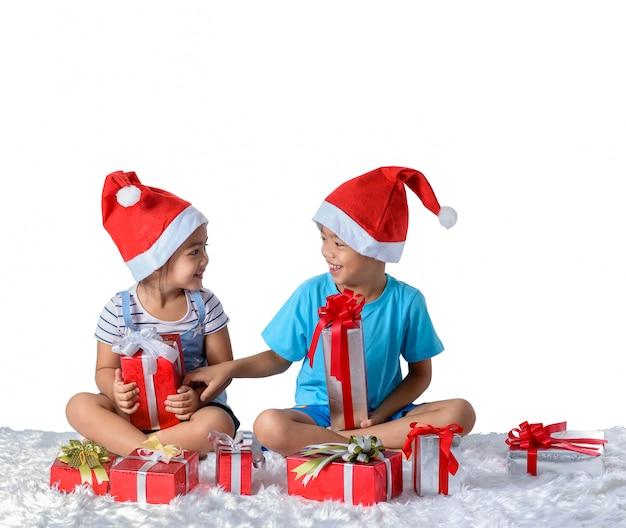 Portret szczęśliwa mała azjatykcia chłopiec i dziewczyna z wiele prezentów pudełkami odizolowywającymi na bielu