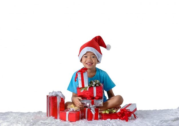 Portret szczęśliwa mała azjatykcia chłopiec z wiele prezentów pudełkami odizolowywającymi na bielu