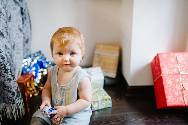 Portret szczęśliwa mała dziewczynka bawi się zabawkami, obok świątecznych prezentów.