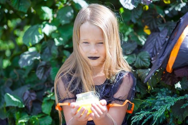 Portret szczęśliwa mała dziewczynka jest ubranym czarownica kostium z miotłą na halloween