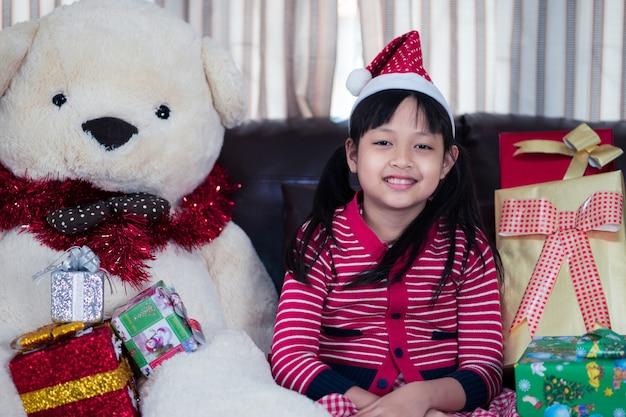 Portret szczęśliwa mała dziewczynka na boże narodzenie kapeluszu z xmas prezentem