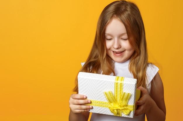 Portret szczęśliwa mała dziewczynka otwiera prezenta pudełko z prezentem.