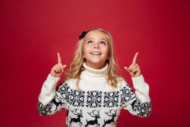 Portret szczęśliwa mała dziewczynka w boże narodzenie pulowerze