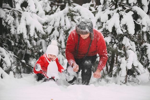 Portret szczęśliwa mała dziewczynka w czerwonym żakiecie z tata ma zabawę z śniegiem w zima lesie. dziewczyna bawi się z tatą.
