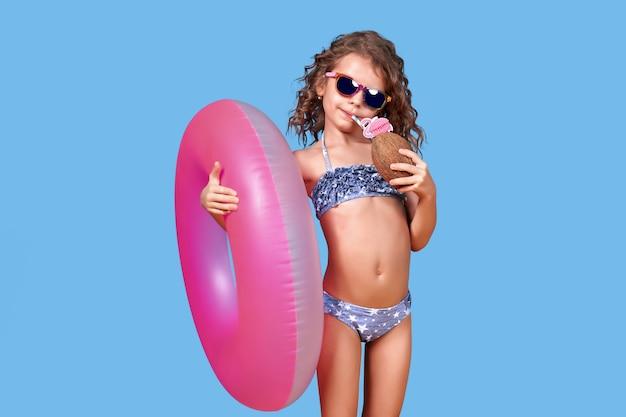 Portret szczęśliwa mała dziewczynka w swimsuit jest ubranym okulary przeciwsłonecznych trzyma nadmuchiwanego pierścionek i kokos z słomą odizolowywającą nad błękitem.
