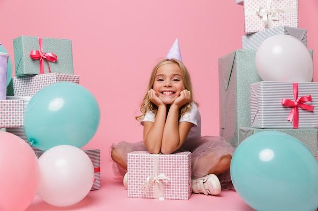 Portret szczęśliwa mała dziewczynka w urodzinowym kapeluszu