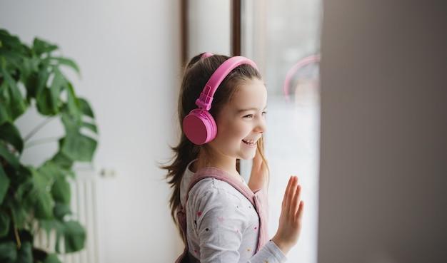 Portret szczęśliwa mała dziewczynka ze słuchawkami w pomieszczeniu w domu, słuchanie muzyki.