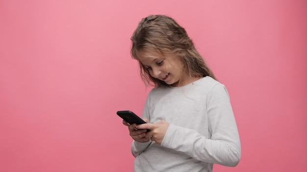 Portret szczęśliwa mała śliczna dziewczyna trzyma smartphone stojąc na różowym tle.