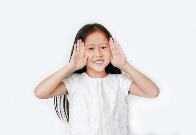 Portret szczęśliwa małe dziecko dziewczyna gestykuluje bawić się peekaboo. postawa dziecka z uśmiechem otwiera ręce przed oczami.