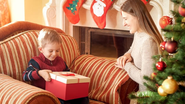 Portret szczęśliwa matka daje prezent na boże narodzenie i piękne pudełko do jej małego synka siedzącego w fotelu obok pięknej choinki. idealny obraz na ferie zimowe i uroczystości