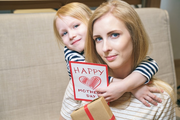 Portret szczęśliwa matka i córka przytulanie i trzymanie karty i prezent w domu. koncepcja dnia matki.