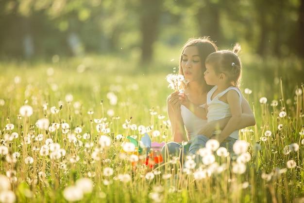 Portret szczęśliwa matka i jej małe dziecko w wiośnie. rozochocona rodzina przy dandelion polem. mama i jej śliczna córka outdoors.