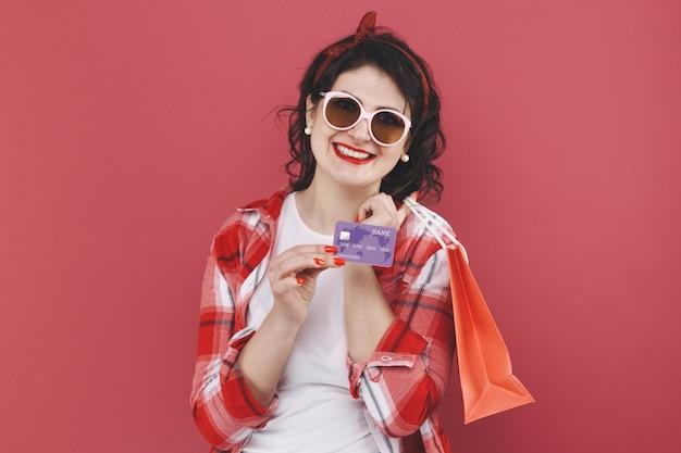 Portret szczęśliwa miła dziewczyna z kręconymi włosami trzymająca torby i kartę kredytową po zakupach na białym tle na żółtym tle