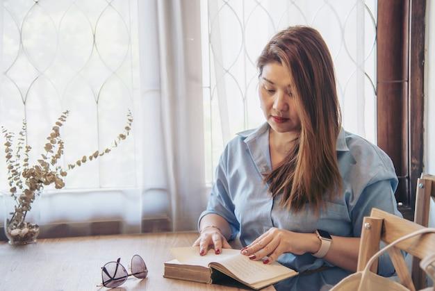 Portret szczęśliwa młoda azjatycka dama w sklep z kawą
