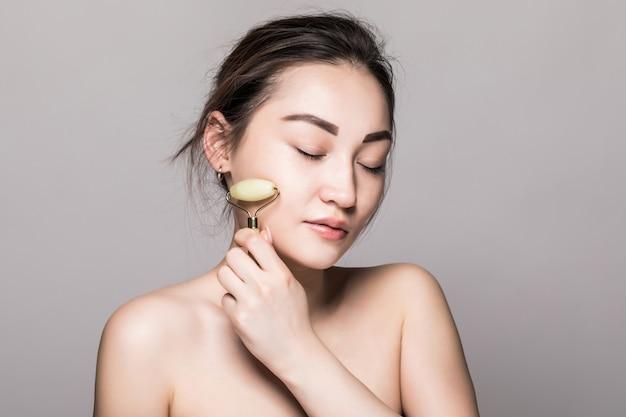 Portret szczęśliwa młoda azjatykcia kobieta bierze opiekę jej skórę i robi masażowi z kosmetologia rolownikiem odizolowywającym na szarości ścianie