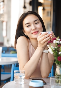 Portret szczęśliwa młoda biznesowa kobieta z kubkiem w rękach picia kawy rano w restauracji