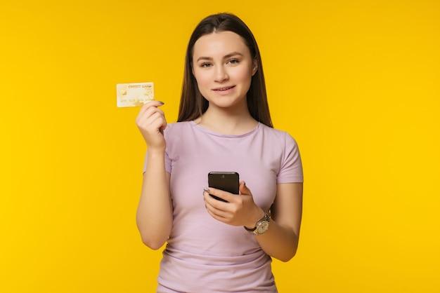 Portret szczęśliwa młoda blondynka pokazuje plastikową kartę kredytową, trzymając telefon komórkowy na żółto