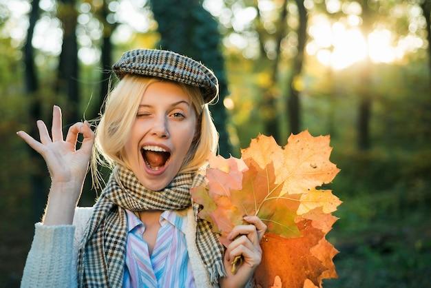 Portret szczęśliwa młoda blondynki dziewczyna pokazuje ok gest i mruga