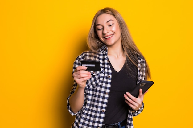 Portret szczęśliwa młoda blondynki kobieta pokazuje plastikową kartę kredytową podczas korzystania z telefonu komórkowego na białym tle nad żółtą ścianą