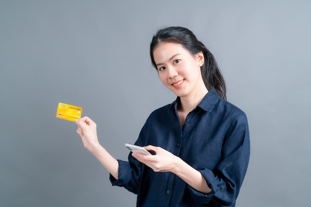 Portret szczęśliwa młoda dziewczyna azjatyckich pokazując plastikową kartę kredytową, trzymając telefon komórkowy na szarej ścianie