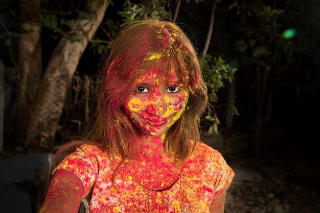 Portret szczęśliwa młoda dziewczyna na festiwalu kolorów holi. dziewczyna pozuje i świętuje festiwal kolorów.