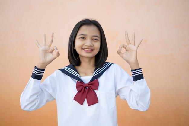 Portret szczęśliwa młoda dziewczyna nosi mundurek w szkole