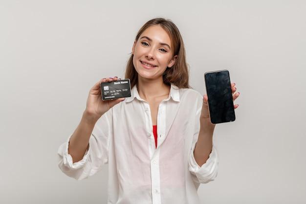 Portret szczęśliwa młoda dziewczyna pokazuje plastikową kartę kredytową trzymającą telefon komórkowy z czarnym ekranem