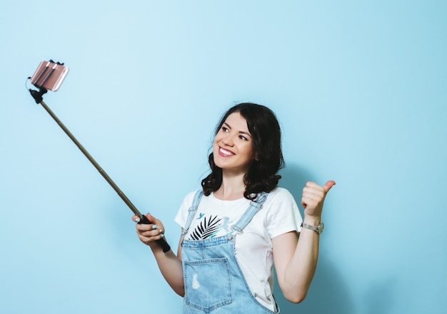 Portret szczęśliwa młoda dziewczyna robi selfie odizolowywającemu nad błękit ścianą
