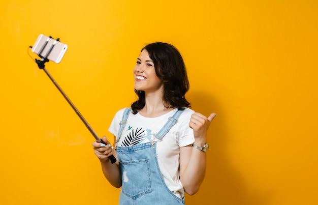 Portret szczęśliwa młoda dziewczyna robi selfie odizolowywającemu nad kolor żółty ścianą