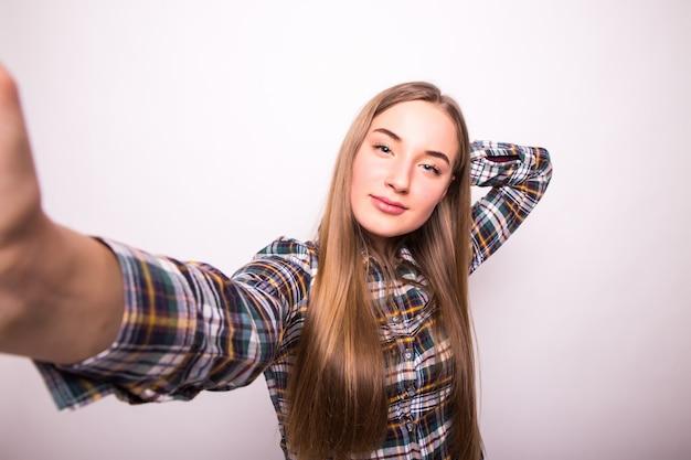 Portret szczęśliwa młoda dziewczyna robi śmieszną minę podczas robienia zdjęć siebie na białym tle nad białą ścianą