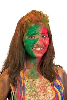 Portret szczęśliwa młoda dziewczyna z kolorową twarzą na festiwalu kolorów holi na białym tle