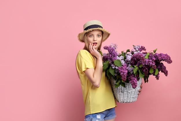 Portret szczęśliwa młoda dziewczyna z koszem pełnym bzu na różowym tle.