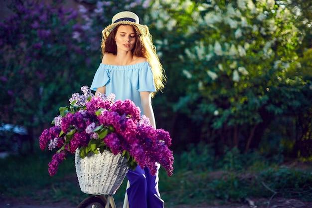 Portret szczęśliwa młoda dziewczyna z rocznika rower i kwiaty na tle miasta w słońcu na zewnątrz.
